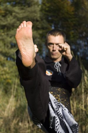 a kick in pencak silat style, where the foot is the only sharp part. Stock Photo - 388636