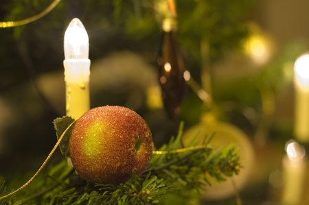 christmas apple with candle in tree. Фото со стока