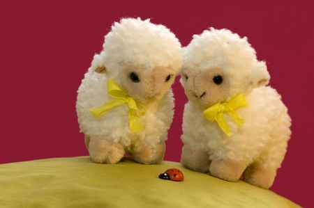 a cute spring picture of two toy sheep on a green hill looking at a ladybird.