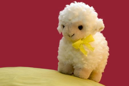 a cute spring picture of a toy sheep on a green hill.