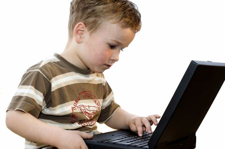 Five year old boy working on a laptop computer.