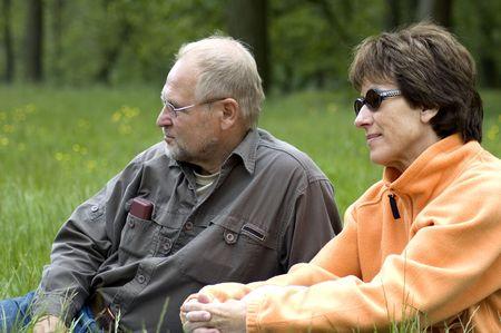 Lovely senior couple enjoying the sun in a green grass field. photo