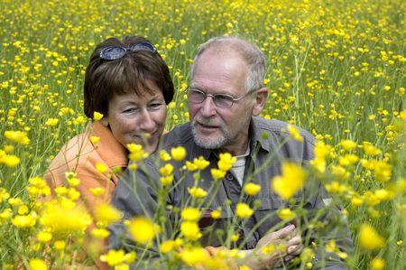 Lovely senior couple enjoying the sun in a green grass field full of buttercups. Фото со стока