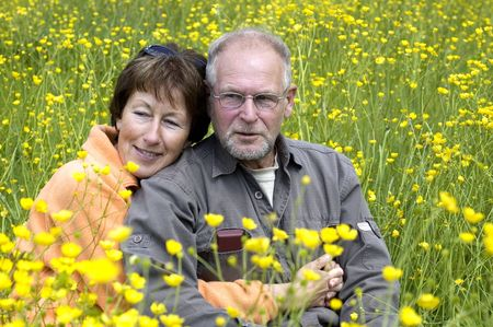 Lovely senior couple enjoying the sun in a green grass field full of buttercups. Фото со стока
