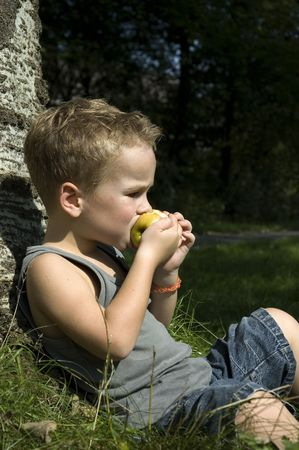 Kid eating a apple while sitting against a tree