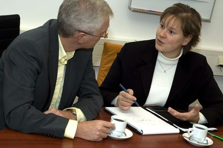 Two business people discussing. Focus is on the woman. Stock Photo