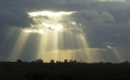 breaking through: Sunbeams romper a trav�s de las nubes en un d�a nublado, con un hermoso horizonte.