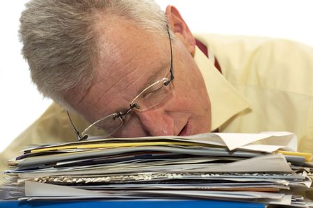 An exhausted senior businessman has fallen asleep on his work. Фото со стока