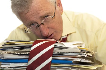 An exhausted businessman has had too much of his paperwork. Фото со стока