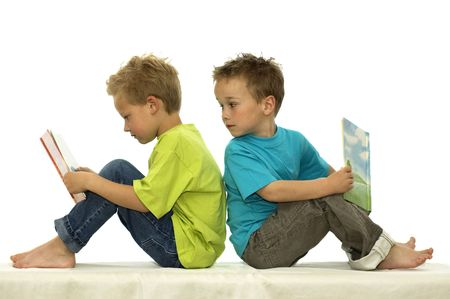 children reading books: Two friends reading a book, one boy looking surprised at the book of the other. Stock Photo