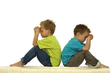 familia en la iglesia: Dos amigos est�n orando mientras estaba sentado con la espalda contra el otro.