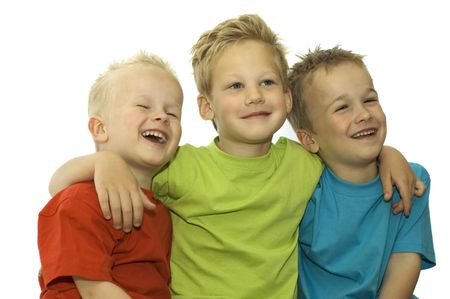 Three friends laughing, holding each other and having fun.