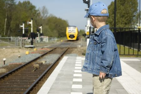 Little boy waiting for the train to come on a railway station. Фото со стока
