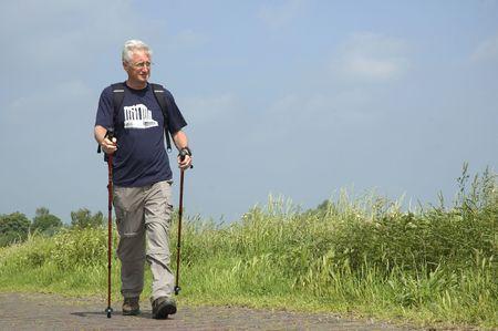 Senior man doing a Nordic Walk on a sunny day. Фото со стока