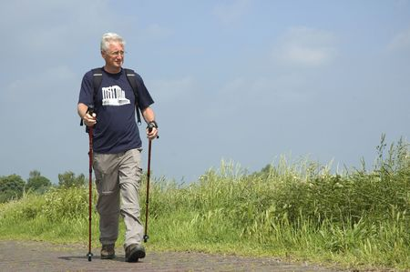 Senior man doing a Nordic Walk on a sunny day. Stock Photo