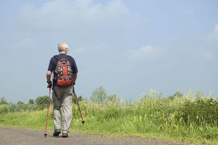 Senior man doing a Nordic Walk in the sun.