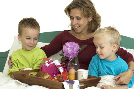 Nice family having a breakfast in bed. It is Mothers Day.