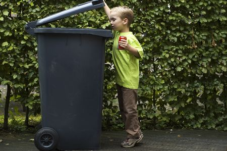 Boy wanting to throw a can in the container, he is learning to be aware that recycling is important.