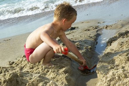 dug: Boy digging a river in the sand of the beach. Nice summer picture. Some movement in the arms and shovel.