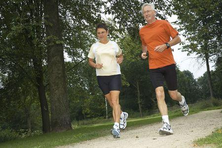 Senior couple running through the woods.