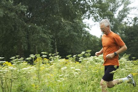 Senior man is running through a field of flowers. Stock Photo