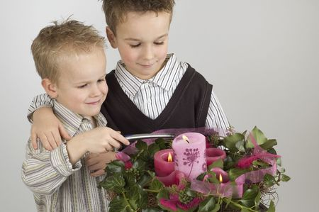 advent candles: Two brothers lighting the Advent candles. Happy  and Christmas picture. Stock Photo