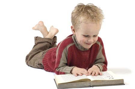 educations: 5 year old reading a book, isolated on white. Book is an old childrens Bible.