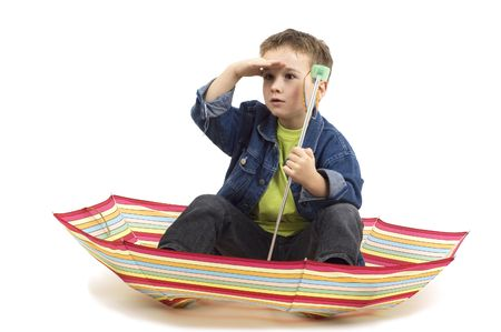 seven year old: Seven year old boy sitting in an umbrella, playing like its a boat. Stock Photo
