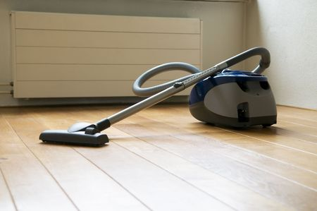 Vacuum cleaner in an empty room, used before moving out of the house.