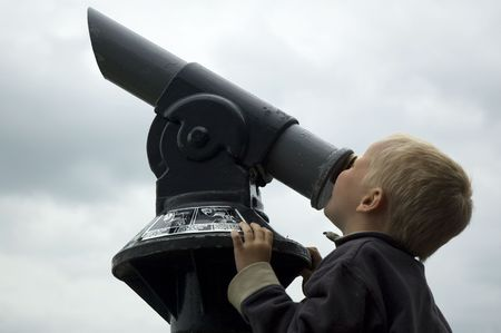 Boy looking into the sky through a telescope. Stock Photo