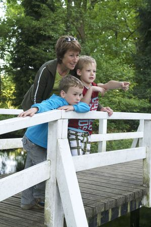 Grandma is standing on a bridge with her two grandsons, looking at a lake. Stock Photo - 3078977