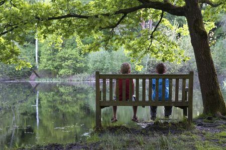 Two friends are sitting on a bench, looking at a lake. Stock Photo - 3078976
