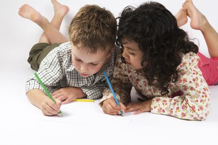 Two friends are drawing together, lying on the floor. photo