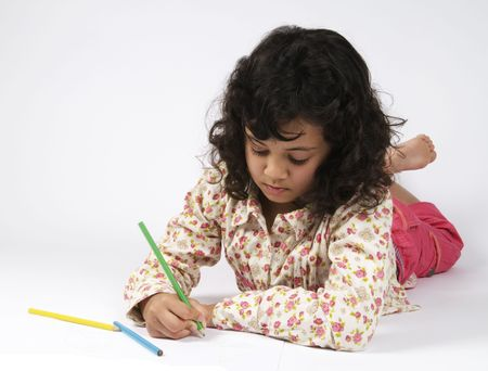 Girl drawing on a sheet of paper, very concentrated. photo