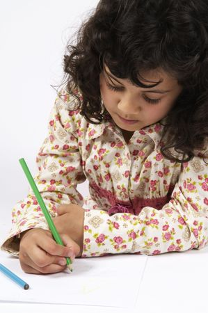 Girl drawing on a sheet of paper, very concentrated. Stock Photo