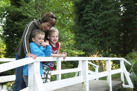 Grandma is standing on a bridge with her two grandsons, looking at a lake. Stock Photo - 3104389