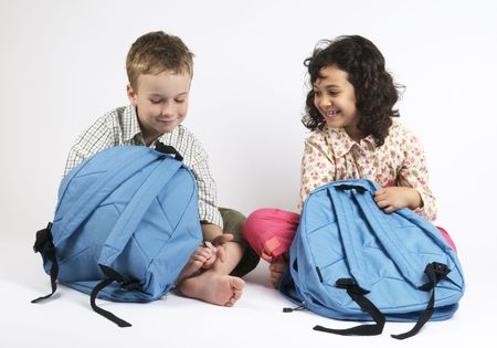 Two kids going on a vacation packing their backpacks. Or use it as two kids packing for school...
