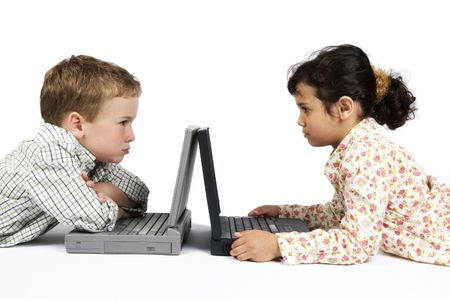 Two kids working on their laptop. Something made them angry... photo