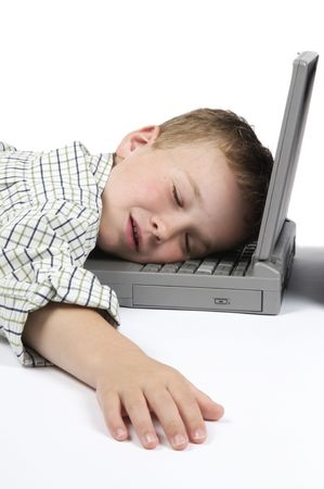 schoolwork: This boy has had too much schoolwork and has fallen asleep on his laptop.