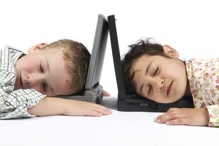 Two kids fallen asleep on their laptops while doing their homework for school. photo