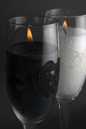 Candles in glasses, against a black background. Stock Photo