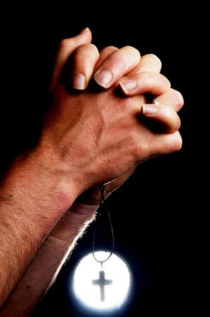 Praying hands holding a cross in front of a bright light. Stockfoto