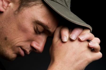 hombre orando: Joven orando, sobre un fondo negro.  Foto de archivo