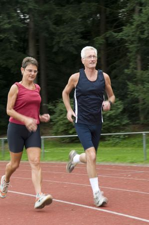 senior couple running on a race track Stock Photo