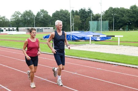 senior olympics: Senior couple running together on a track in a stadium.