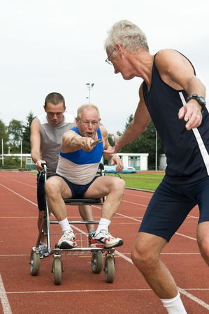 disabled sports: Disabled person and his helper reaching for an other athlete to pass him the baton. Caricature picture to illustrate helping, giving, disabilty, ability, getting older, not wanna quit. Stock Photo