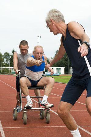 relevos: Persona con discapacidad y su ayudante para llegar a un atleta a otro le pase el relevo. Foto caricatura para ilustrar ayudar, dar, disabilty, la capacidad, envejeciendo, no quieren dejar de fumar.