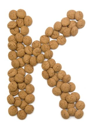 pepernoot: Little ginger nuts in the form of the letter K. These little ginger nuts are used in Holland for the Sinterklaas party, which is at Dec 5 every year. Sinterklaas is a sort of Santa Claus. In Holland these ginger nuts are called pepernoot. Isolated on