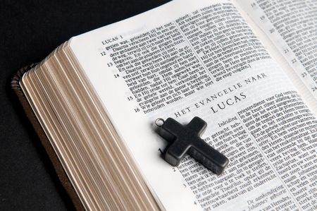 Closeup of Dutch Bible with cross, on black background.