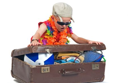 Little boy trying to fit all his stuff for the summer vacation in his suitcase.